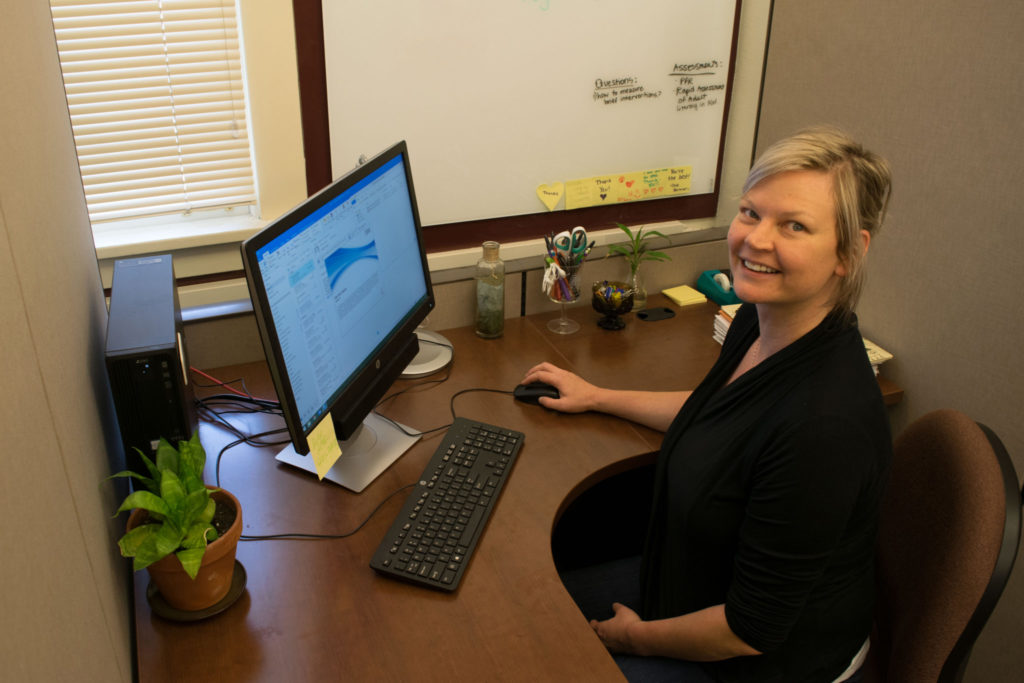 An Occupational Therapy Ph.D student works in her cubicle in the Occupational Therapy Research Annex.
