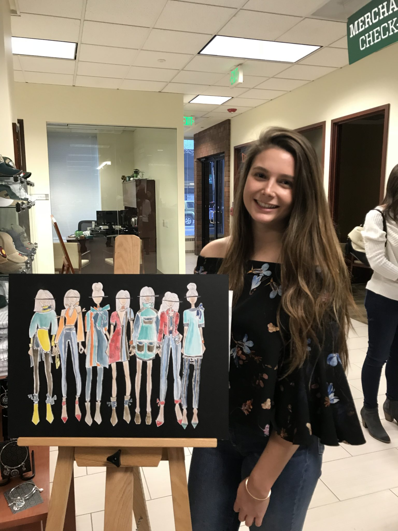 Michaela Coleman poses with her clothing collection illustrations