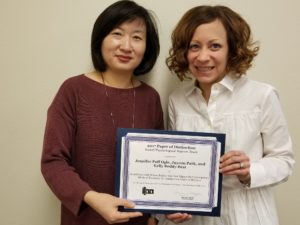 Faculty holding award certificate