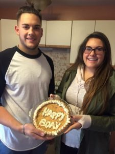 Marisa Gallardo and her brother holding a cake
