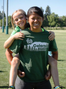 A Youth Sport Camp counselor gives a young girl a piggy-back-ride