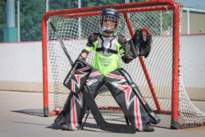 A young boy smiles as he wears his hockey goalie uniform