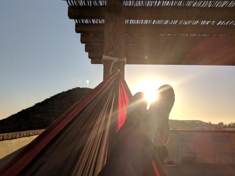 Student resting in hammock watching the sun rise