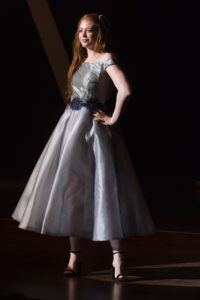 An elegant gray dress with belted a-line skirt and off-the-shoulder bodice.