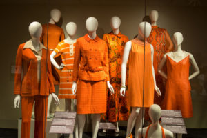 Eight mannequins stand in a cluster, all bedecked in orange from the last century.