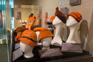 Several mannequin heads wearing orange hats of various materials and shapes.
