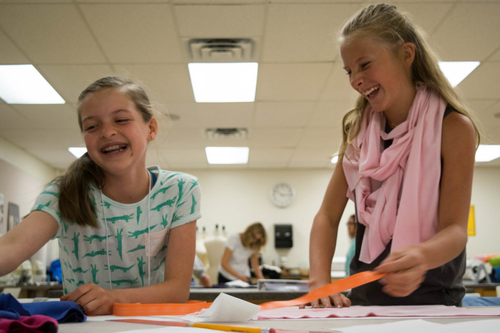 Two girls laugh as they work together on a project.