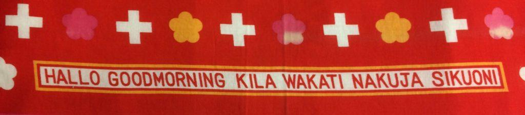 Red Tapestry embroidered with the English and Kiswahili words HALLO GOODMORNING KILA WAKATI NAKUJA SIKUONI embroidered at its base.