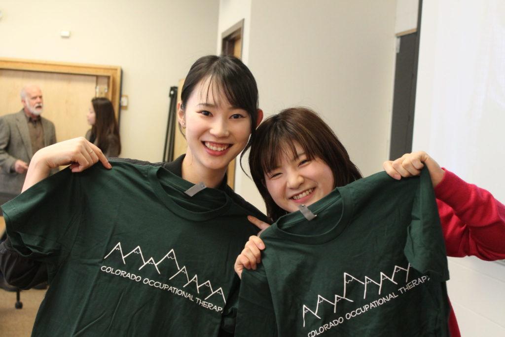 Two visitors holding CSU OT t-shirts