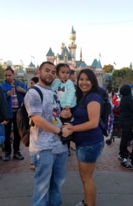 Darian with his wife and daughter outdoors at Disneyland