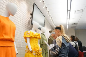 Middle school girls look at dresses through the decades at the Fashion FUNdamentals camp.
