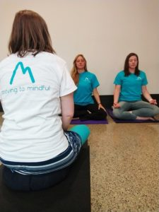 3 women practicing yoga in a Moving to Mindful session.