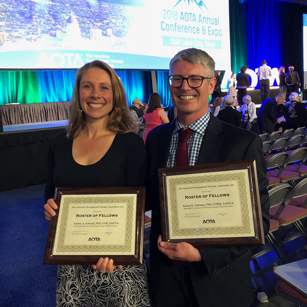 Arlene Schmid and Aaron Eakman with recognition plaques