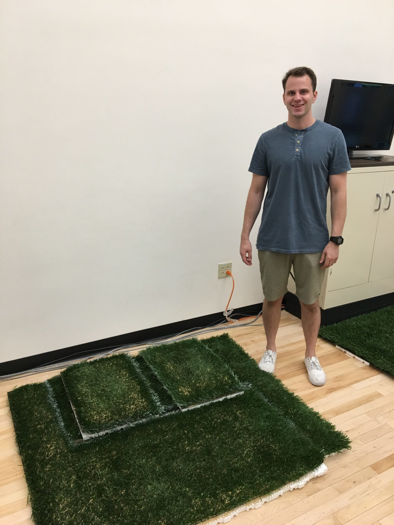 Austin standing and smiling beside a turf used for research.