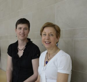 becky orsi and karen barrett sitting in a hallway on campus