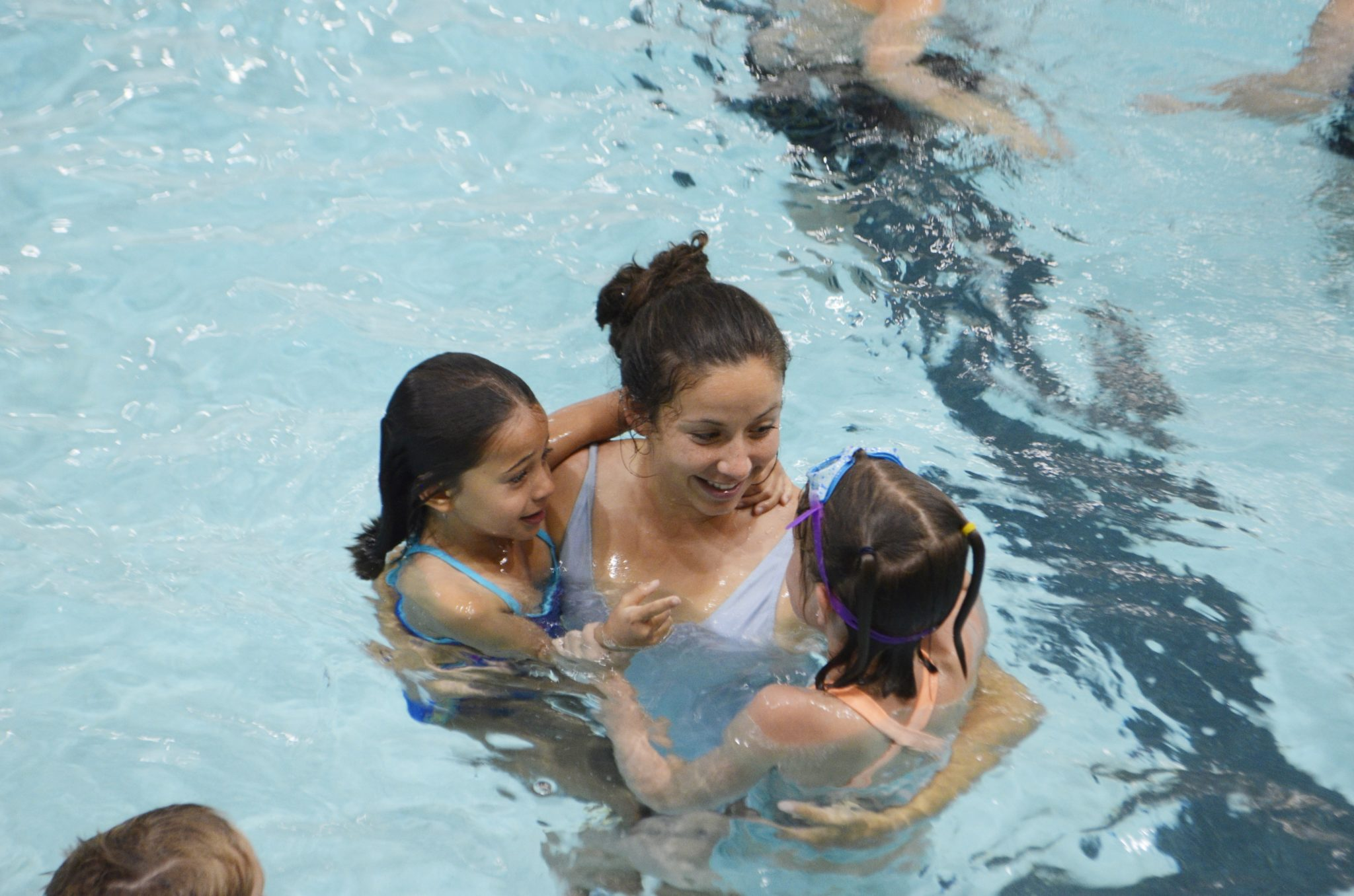 A counselor holds two girls to her hips as they all swim together in the pool at CSU's Moby Arena.