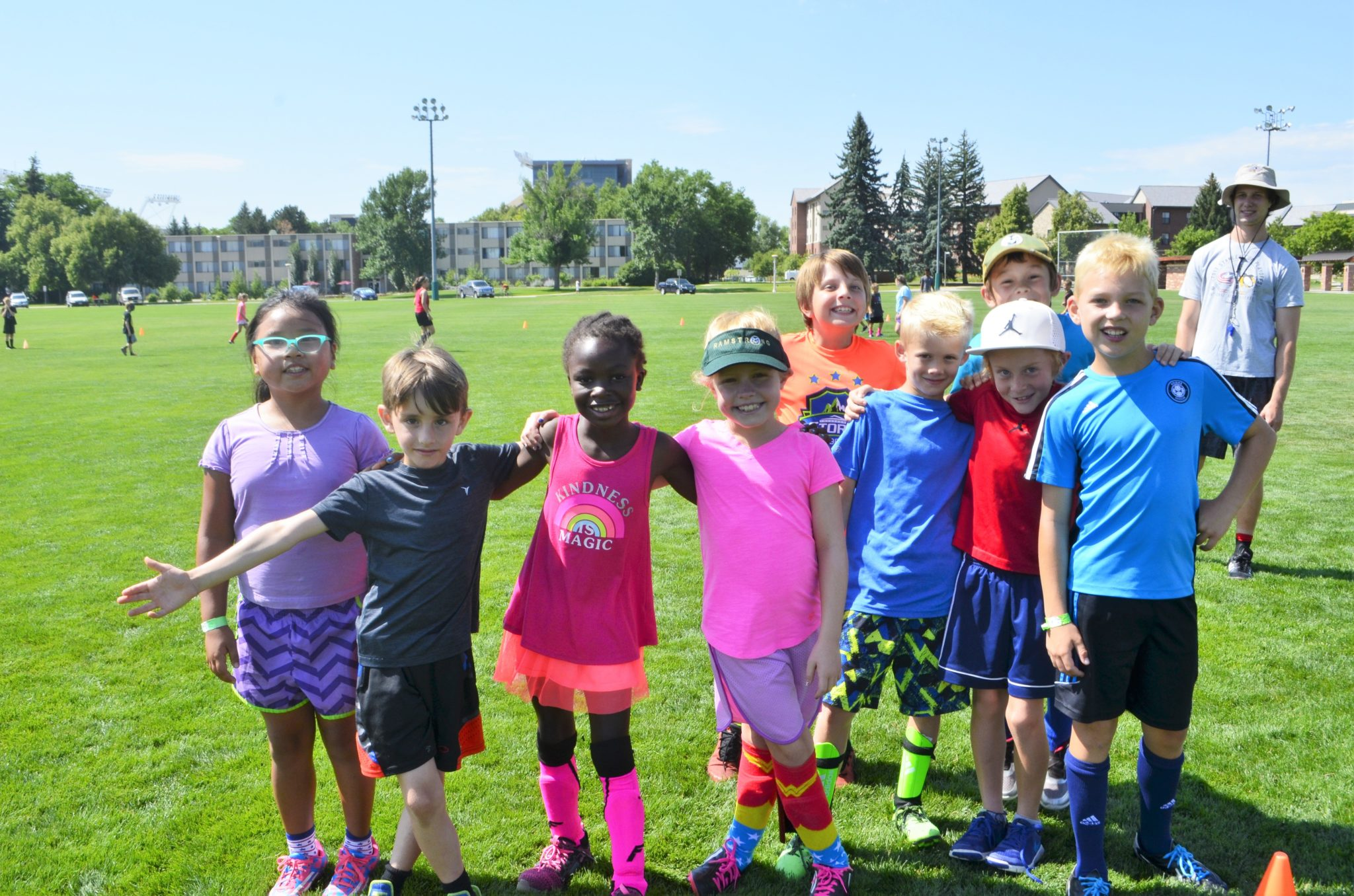 A diverse array of kids in bright colored clothing smile for the camera on the IM fields at CSU.