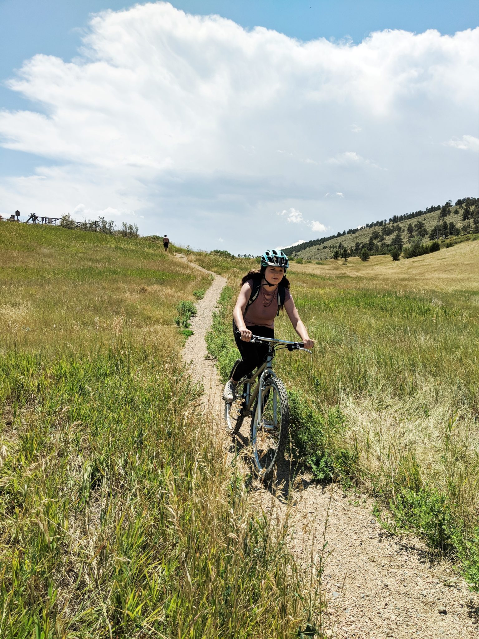 A girl rides a mountain bike down a single track trail surrounded by green fields and trees.