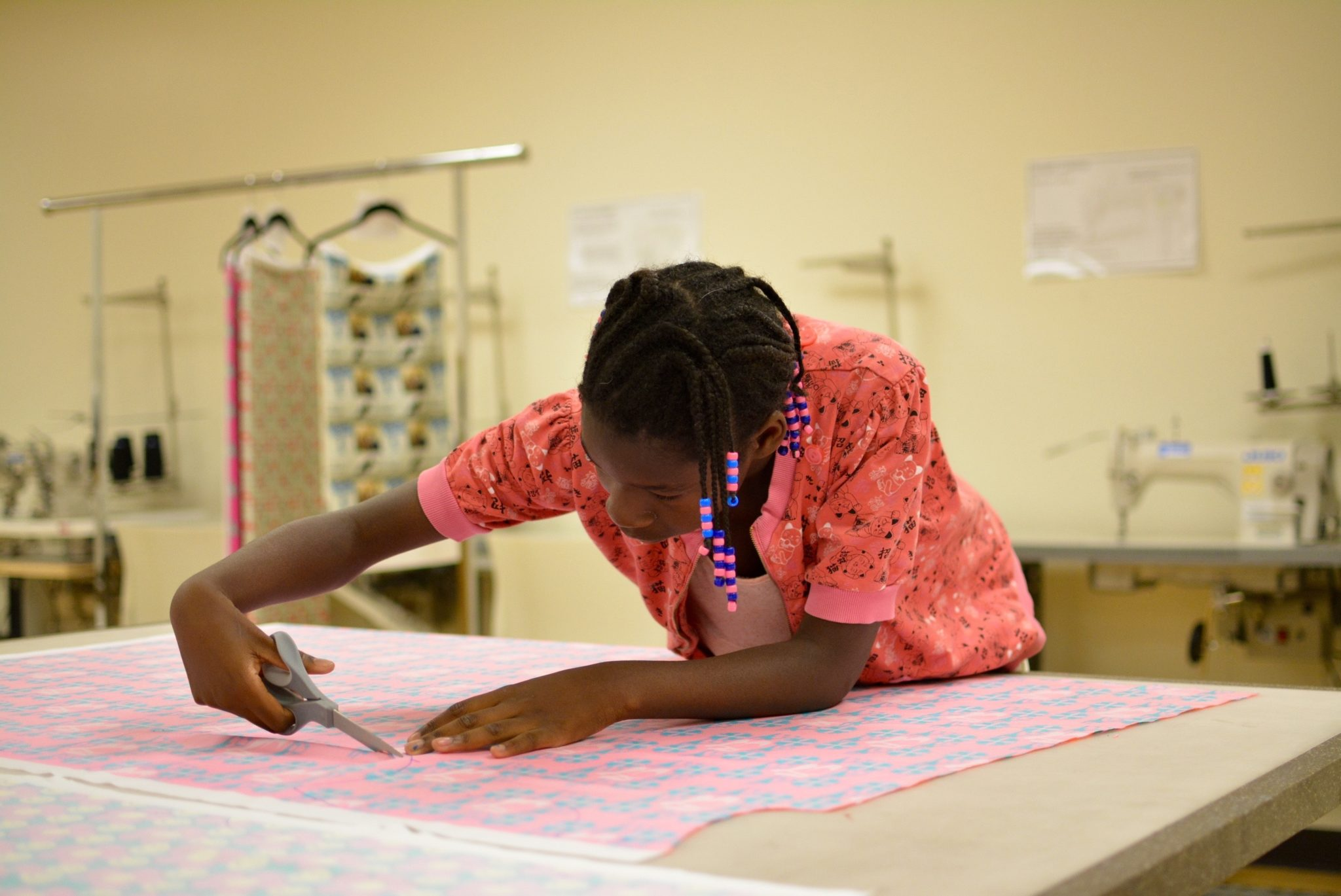 An African American student wearing a peach top leans forward to cut into a piece of patterned fabric.