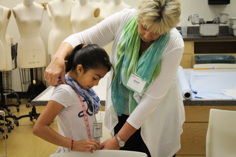 An girl gets help from a staff member to learn how to accurately measure her body proportions.