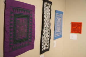 Four Hmong textiles hanging in the Avenir Museum