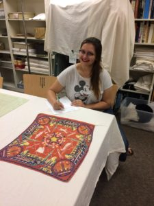 Kim Selinske working with a textile at the Avenir Museum