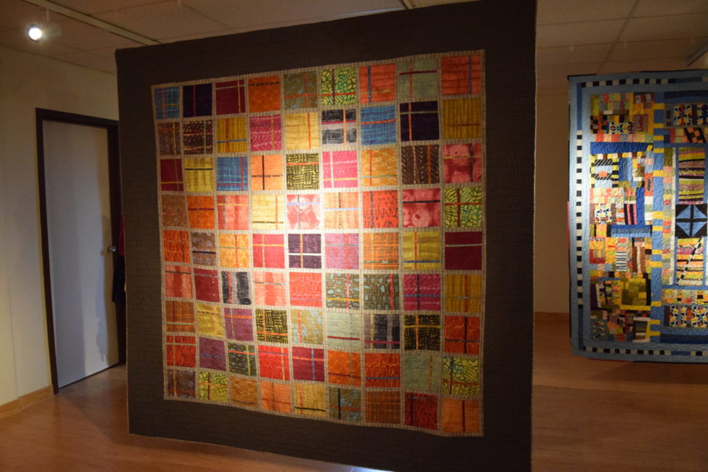 A colorful quilt with striated patterns in the squares.
