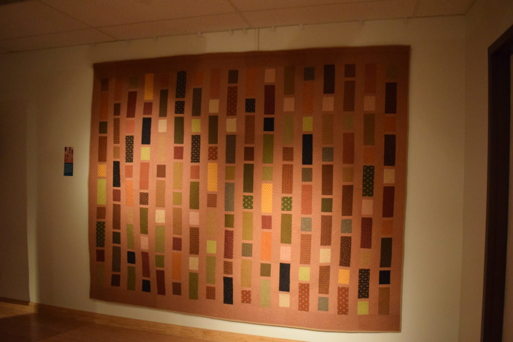A earth-toned quilt with vertically oriented strips of alternating colored fabric.