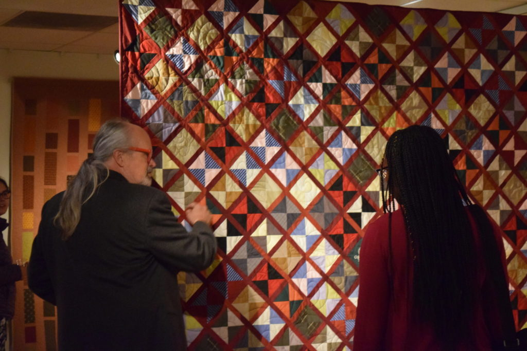 Vistors to the Gustafson Gallery admire the quilts.