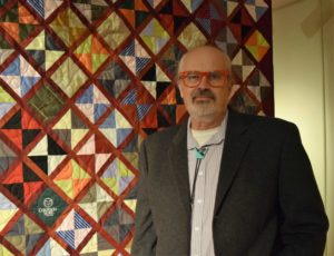 Jeff Miller, standing in front of one of the his quilts in the Gustafson Gallery.
