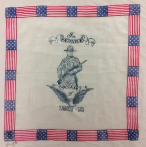 "A handkerchief bordered in american flags shows a gray print of a soldier beaing a rifle. below him is an eagle and the years ""1917-18."""
