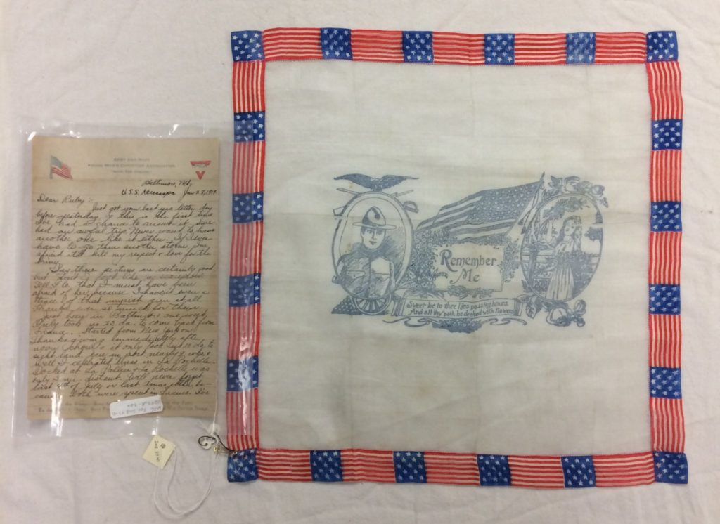 "A handkerchief bordered in american flags shows a gray print of a young man and woman. In the center of the handkerchief it reads ""Remember Me"" with more text below that that says ""Sweet be thee life's passing hours, and all thy path be decked with flowers."""