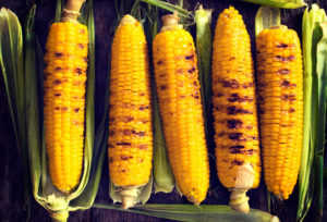 Grilled young corn from above on a wooden table top.