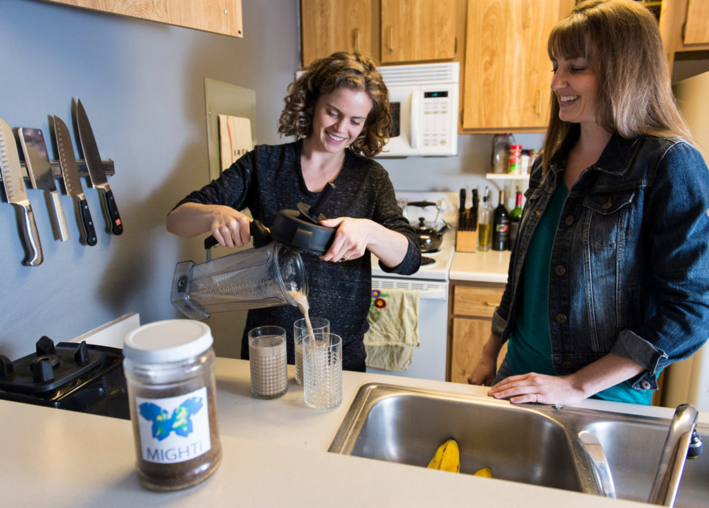 Two women pour a beverage in the test kitchen.