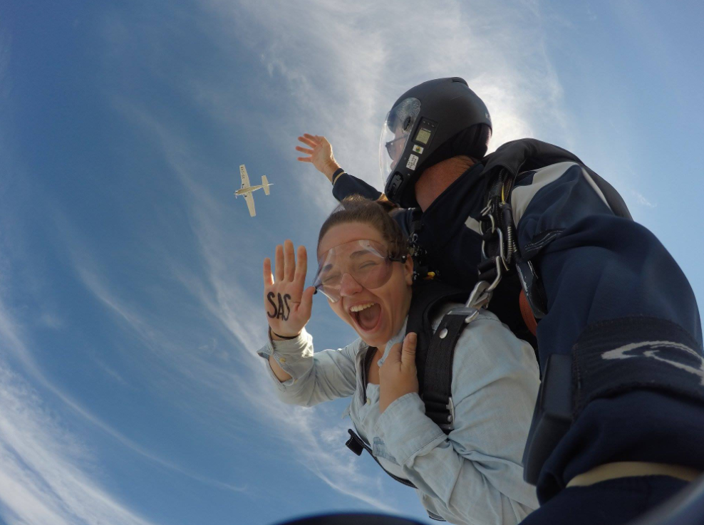 A girl laughing after jumping out of a plane strapped to an instructor and parachute.