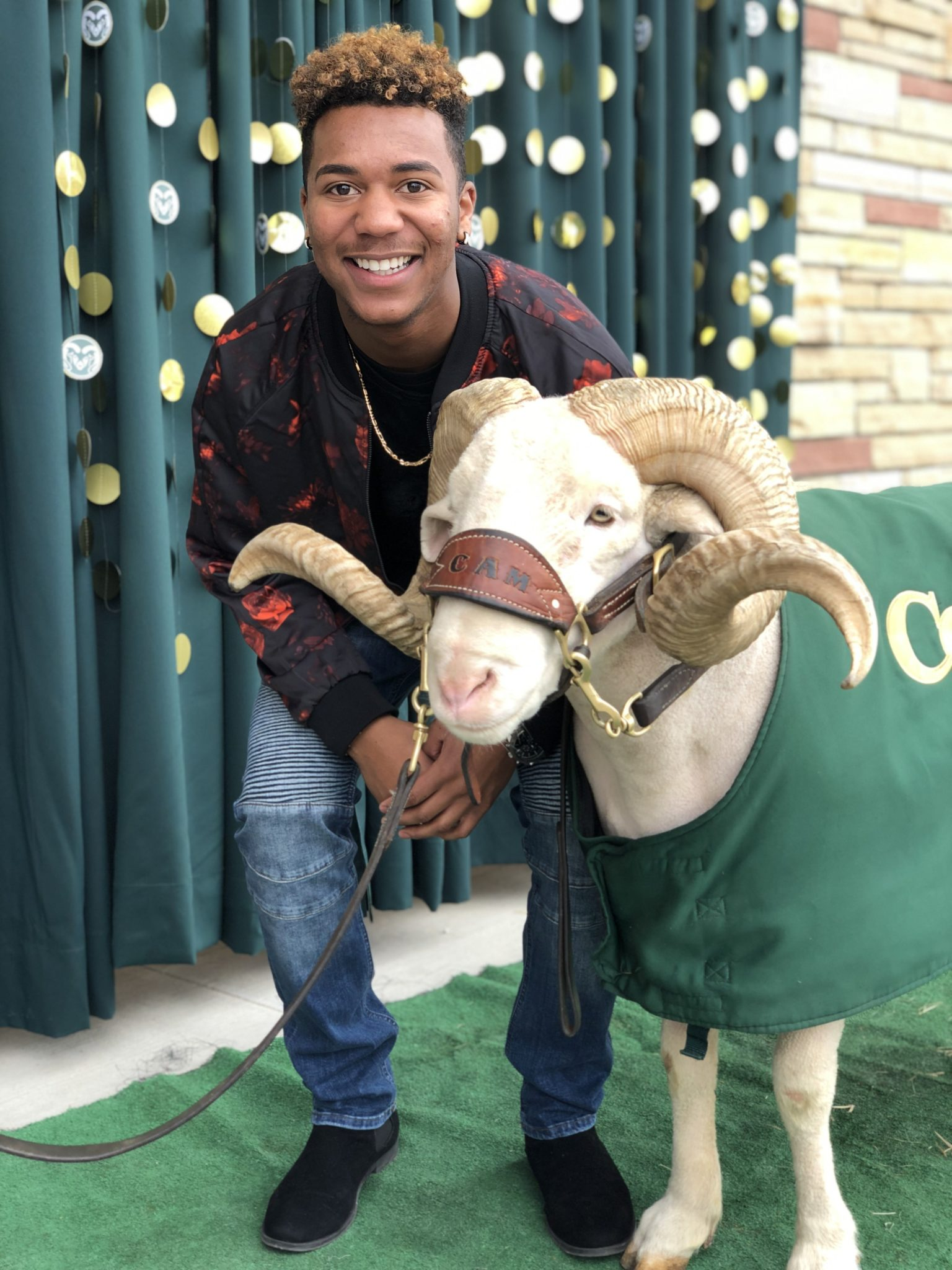 D.J. Chapa in a red sweater smiling with Cam the Ram.
