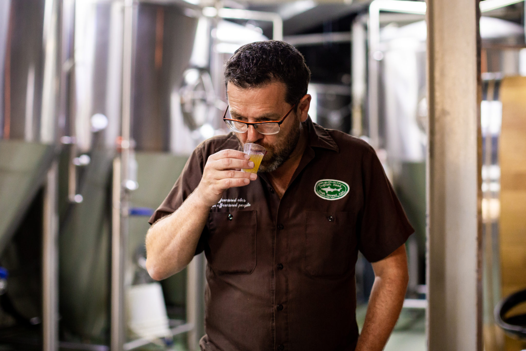 Floris in a brown polo sips beer from a small tasting class in front of brewing equipment.