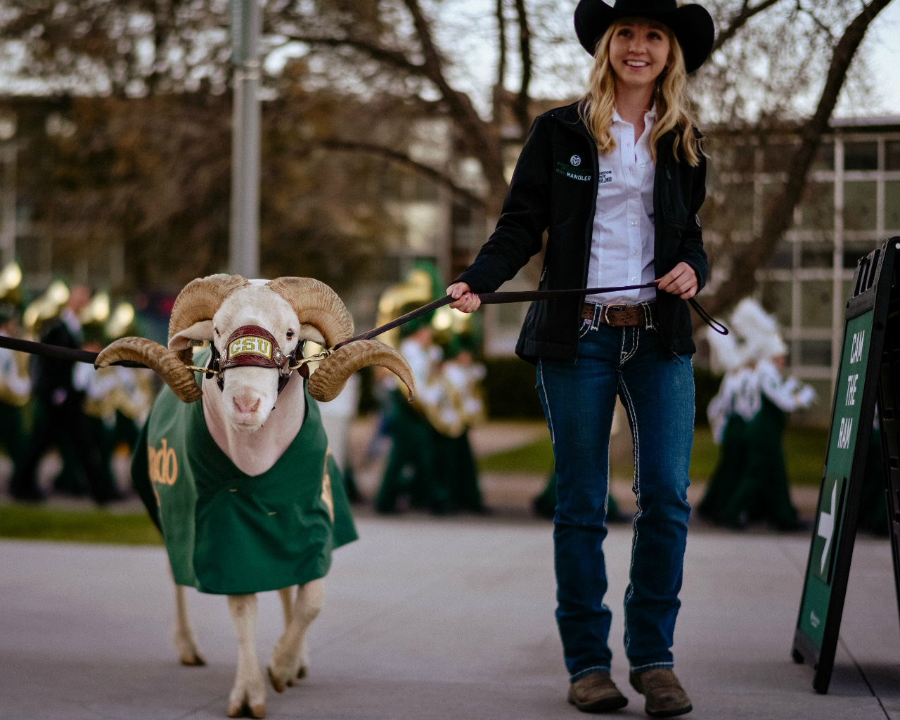 Jillian, a blonde girl in a cowboy hat and boots guides Cam the Ram near the new stadium.