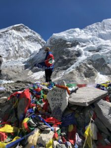 "Cunningham stands in front of a rock painted to read ""Everest Base Camp 2018."" She wears her Colorado flag."