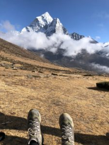 Cunningham's hiking boots sit in the foreground as she rests and admires the mountain peak.
