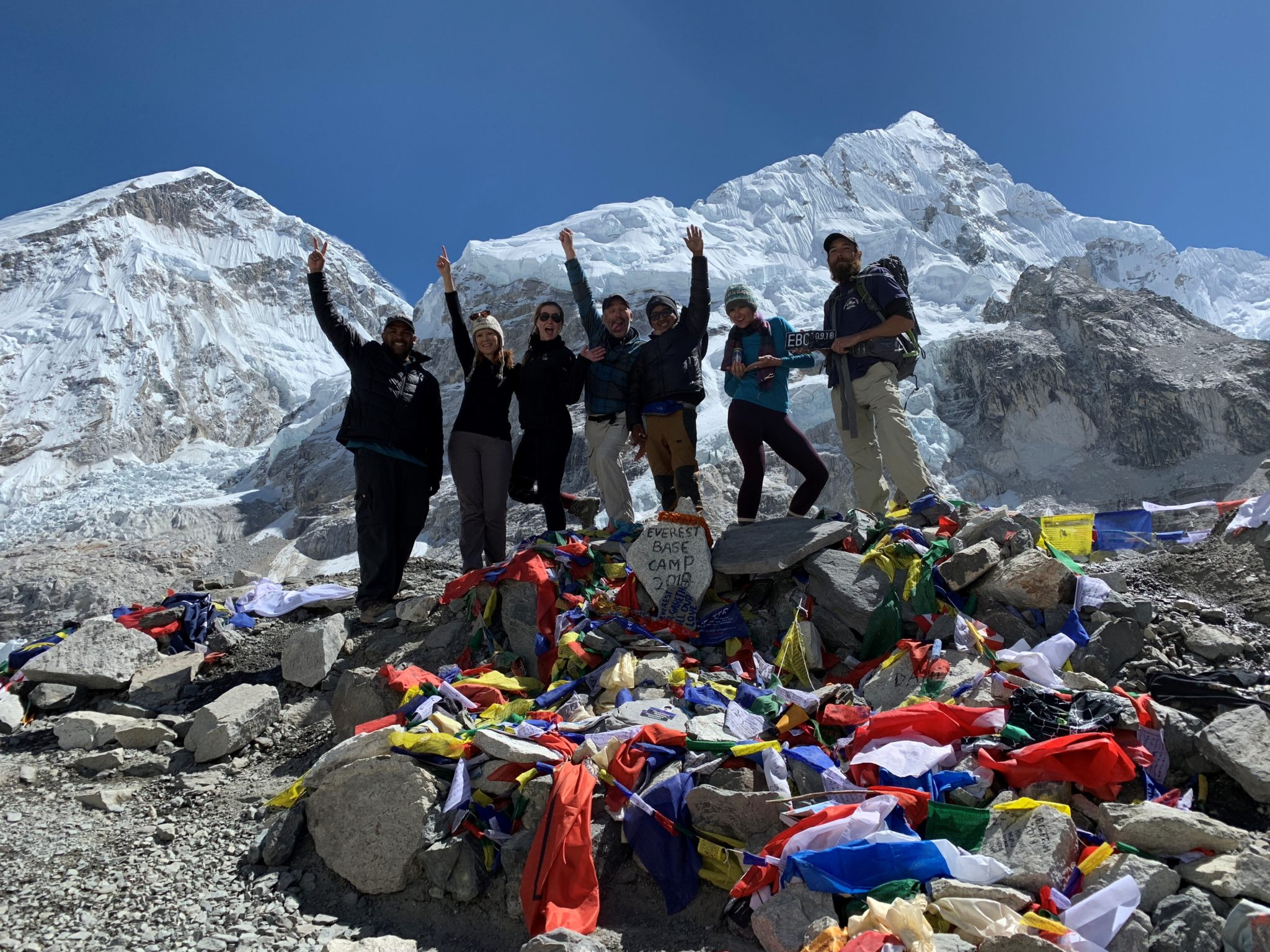 "The entire trekking group stands in front of the ""Everest Base Camp"" sign."
