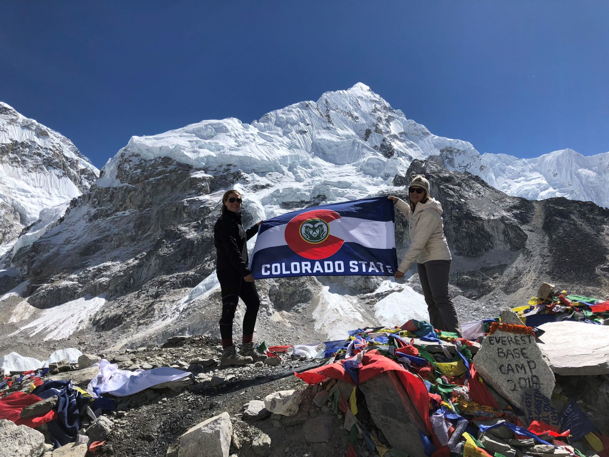 Cunningham proudly stands at the Everest base camp with CSU Alumni Amy Gane while the pair hold Cunningham's Colorado flag. The ground is covered in other flags that travelers have left behind to decorate the base camp.
