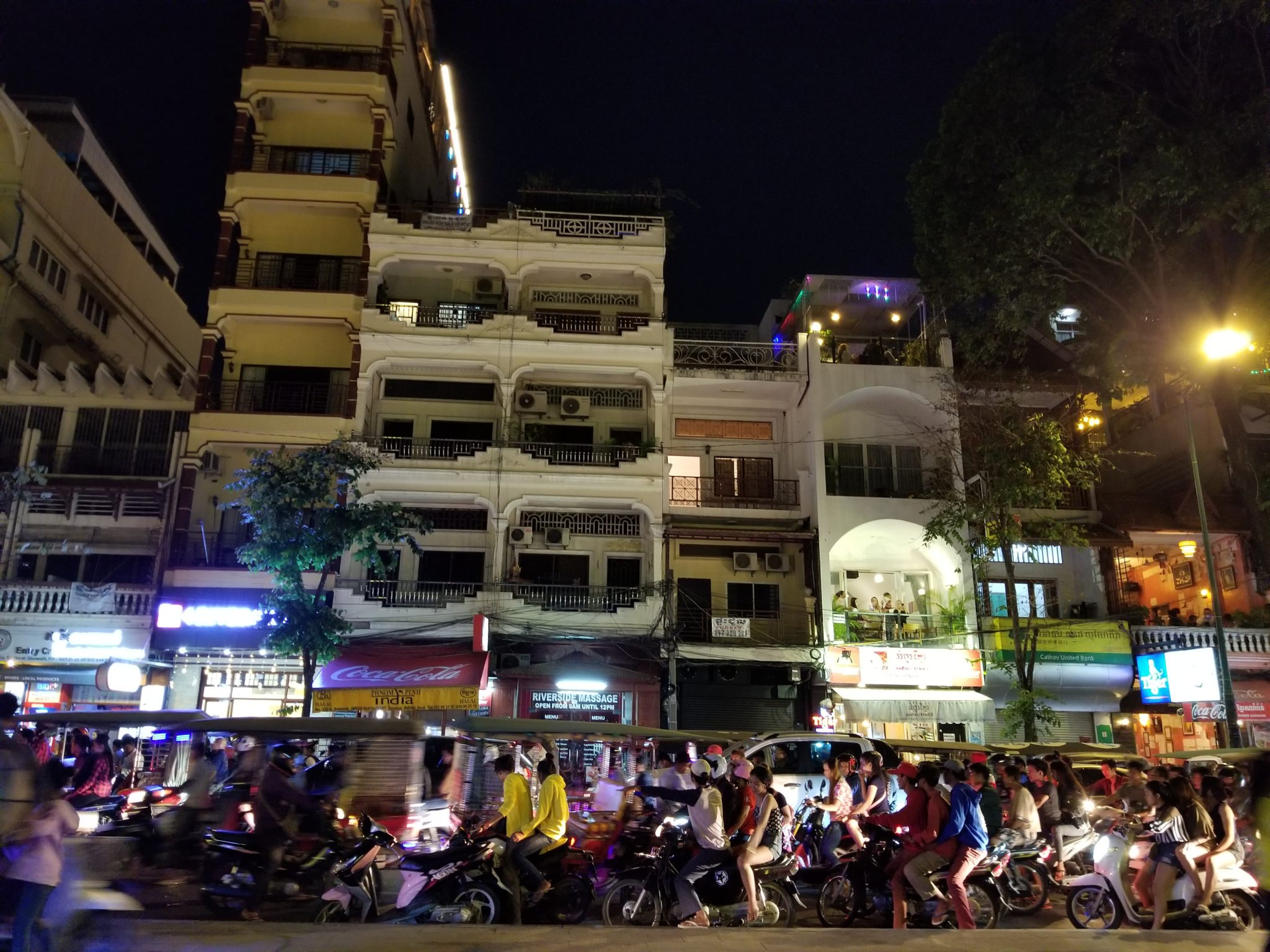A busy street at night, packed with mopeds and tall buildings.