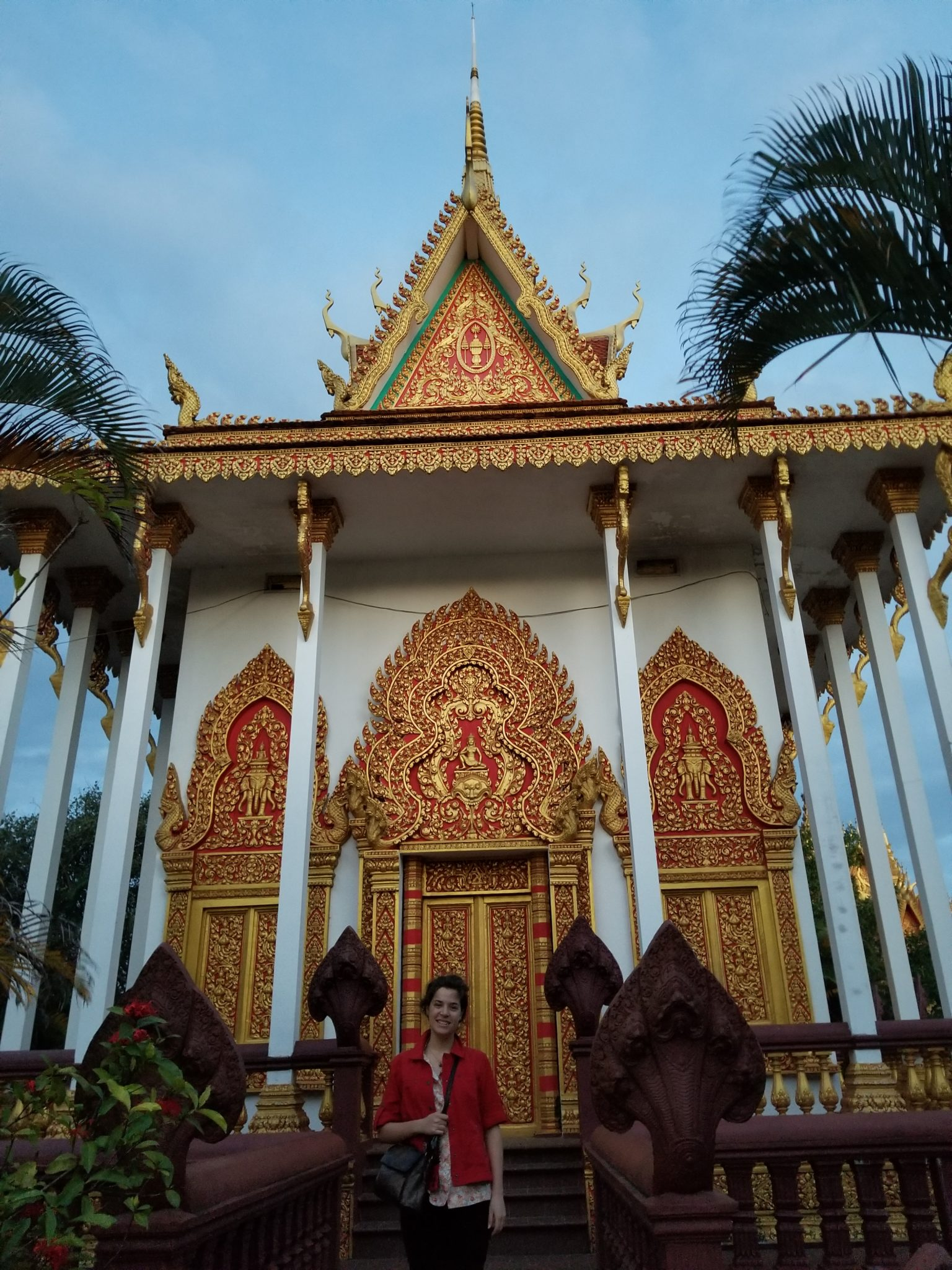 Siedemann in a red jacket in front of a gold and white Cambodian structure