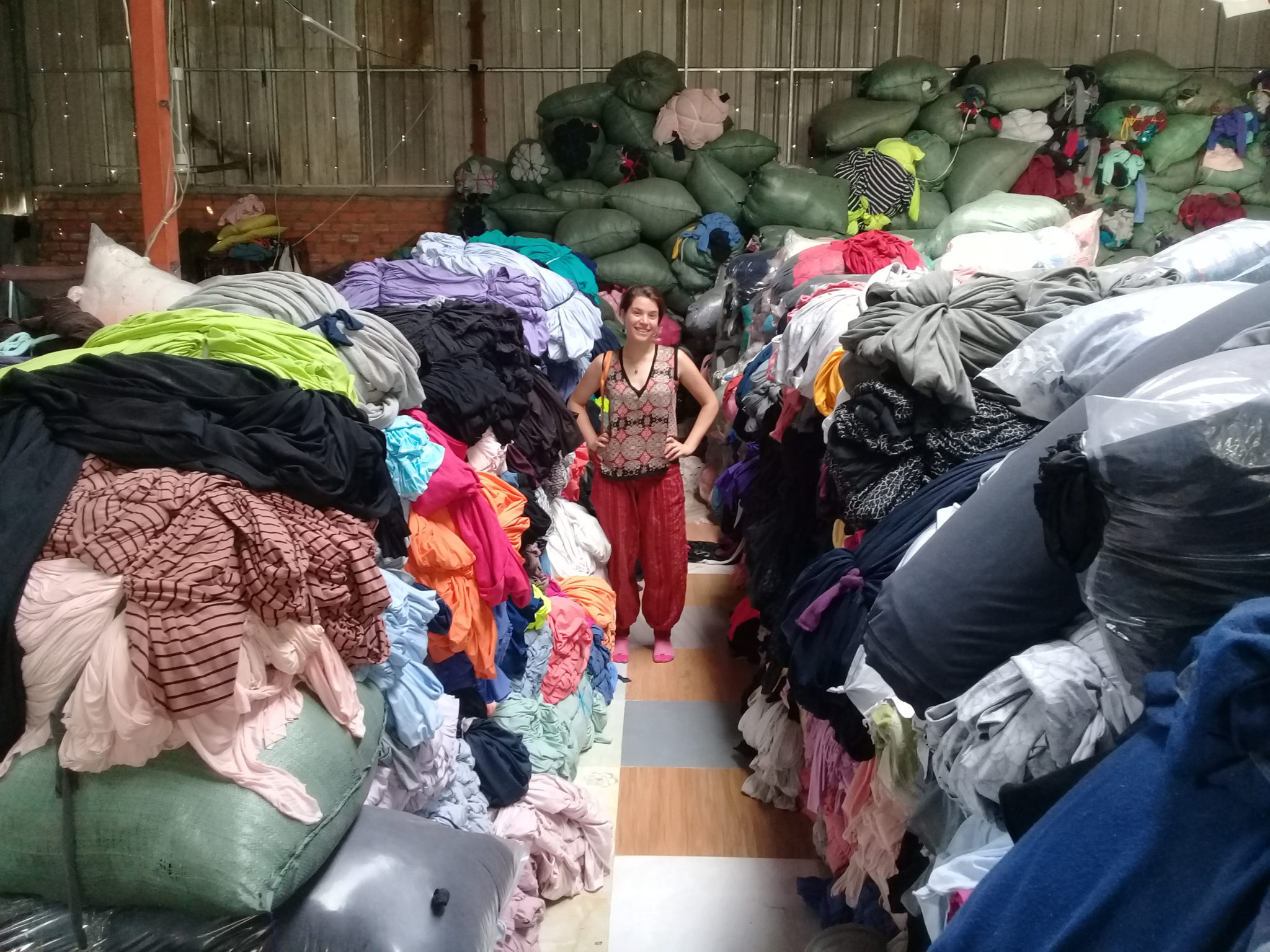Siedemann stands amidst piles of used and wasted clothing.