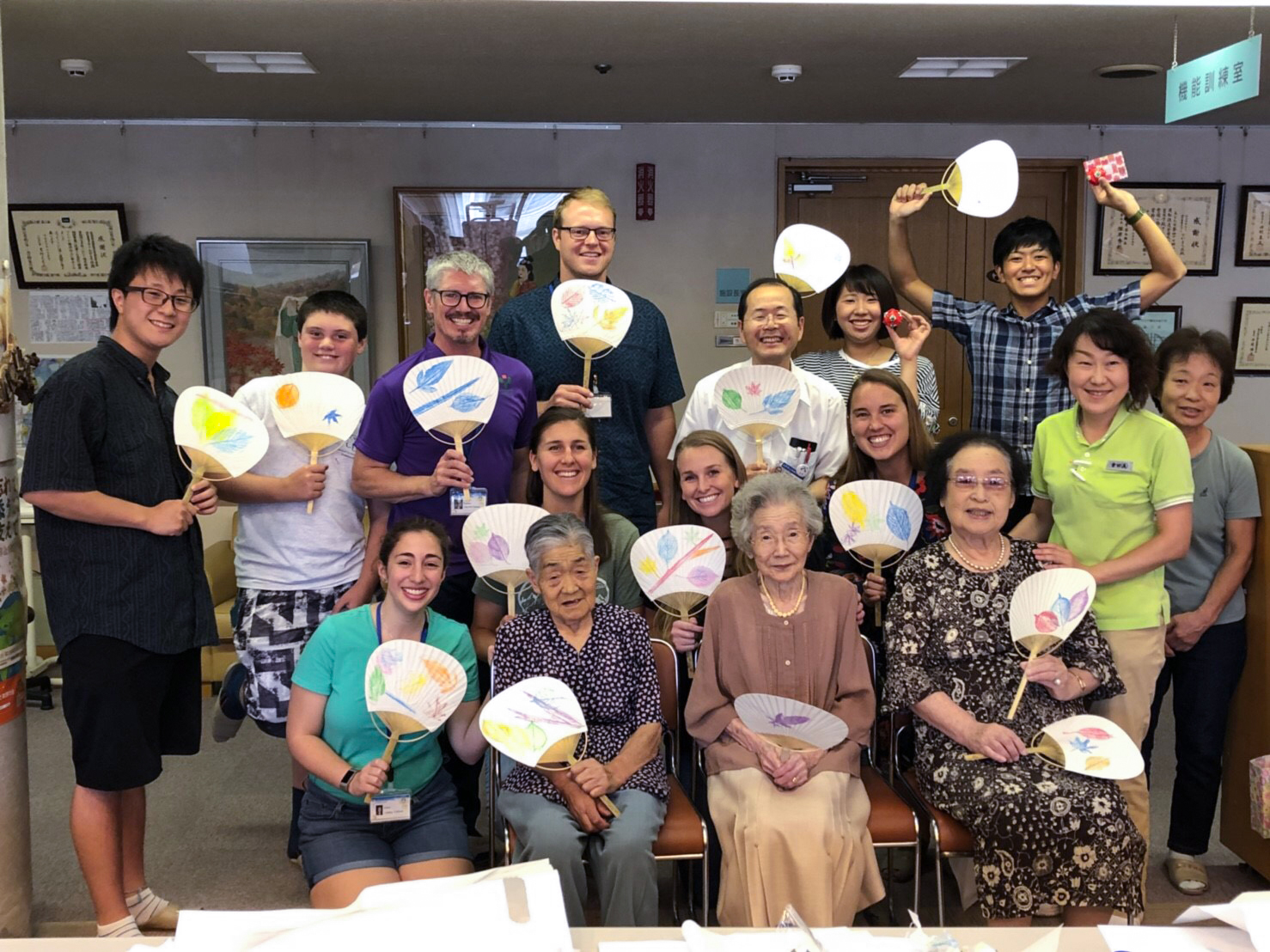 Group holding Japanese fans at nursing home