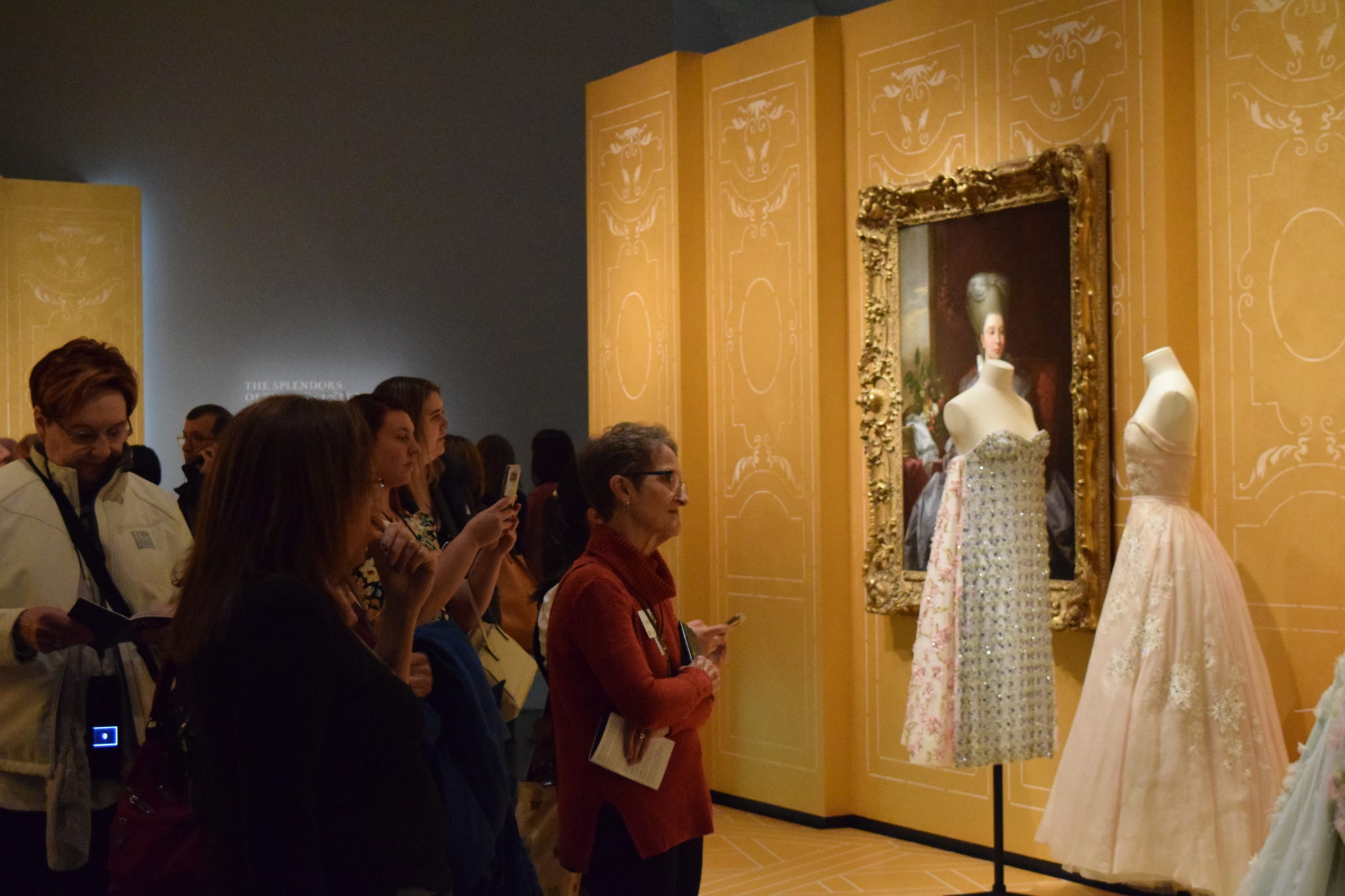 Guests view intricate Dior garments.