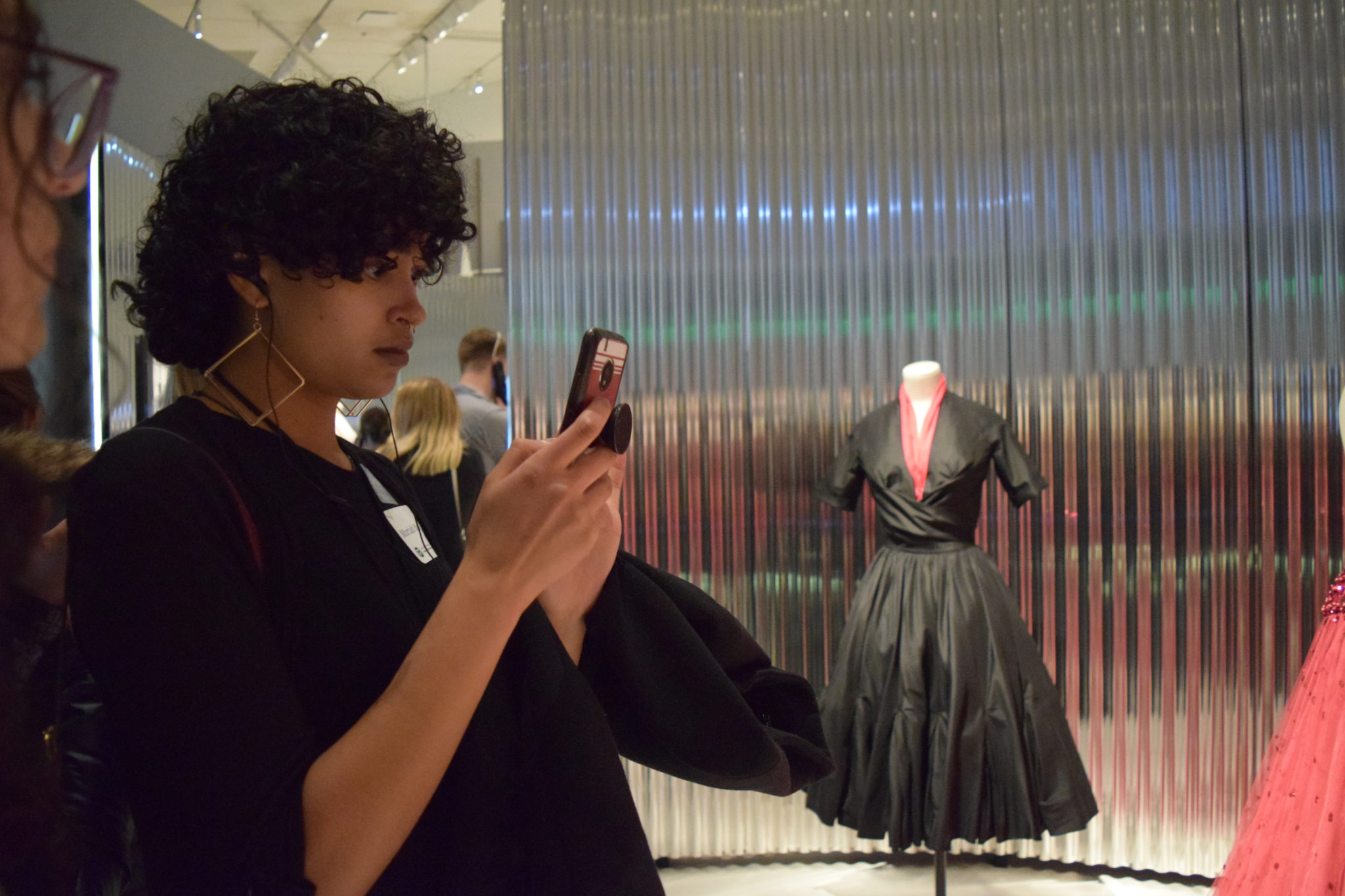 A student uses their cell phone to photograph a garment on display.