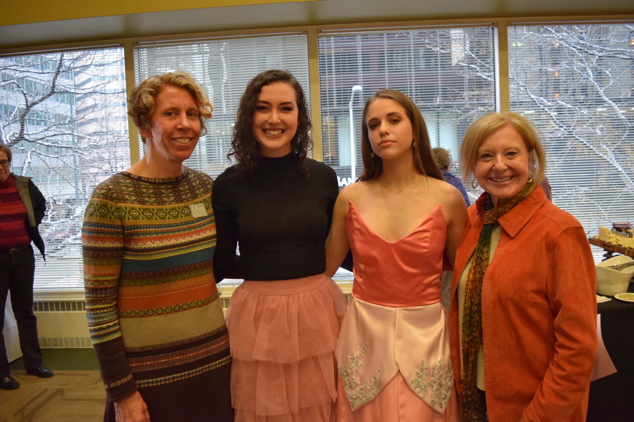 Student designer and student model stand for a photo with Karen Hildegarde and retired Dean
