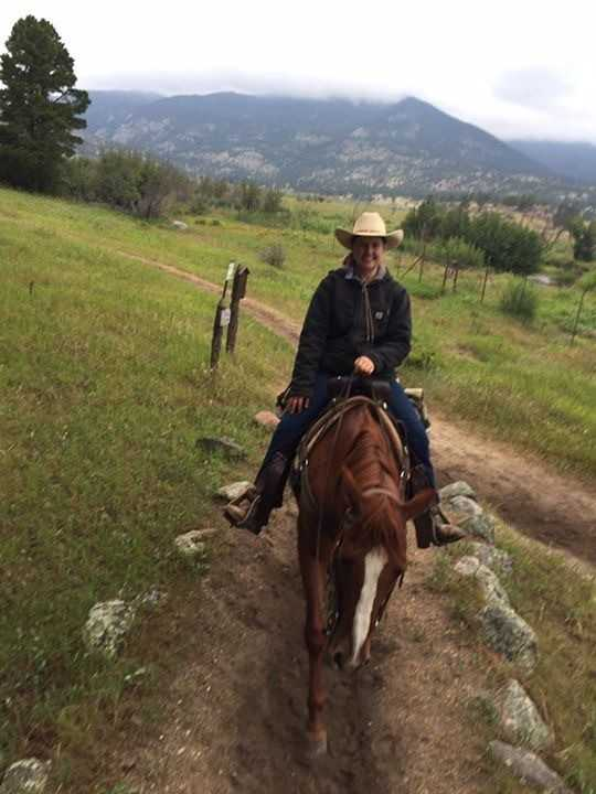 Kyla riding her horse on a mountain trail